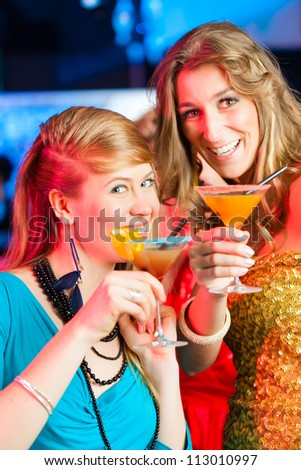 Young women in club or bar drinking cocktails and having fun