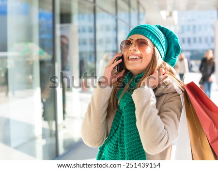Young women in shopping, talking by phone - stock photo