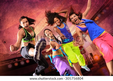 young women in sport dress jumping at an aerobic or fitness exercise - stock photo