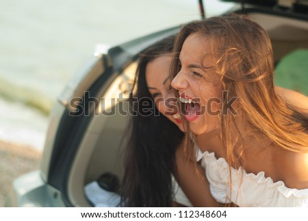 young women in the car smiling - stock photo