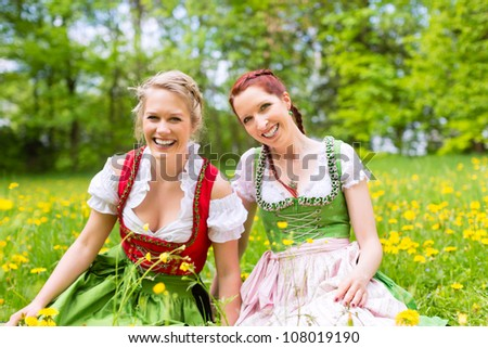 Young women in traditional Bavarian clothes - dirndl or tracht - on a meadow in spring - stock photo