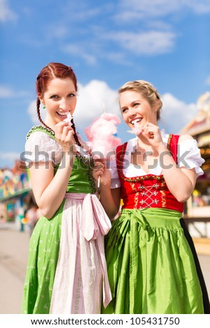 Young women in traditional Bavarian clothes - dirndl or tracht - with candyfloss on a festival or Oktoberfest - stock photo