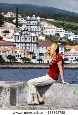 Young women is sitting at the pier of the Marina in Horta  Faial Island, Azores - stock photo