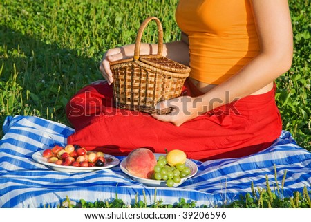 Young Women keeps in hand basket on glade - stock photo