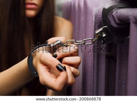 Young women locked with handcuffs to radiator - stock photo