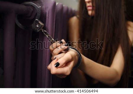 Young women locked with handcuffs to radiator