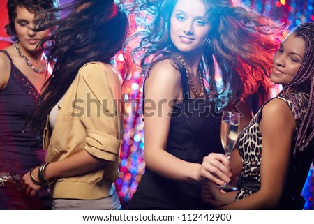 Young women looking at camera while dancing at nightclub