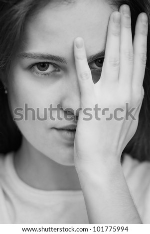 Young women looking through  fingers, monochrome picture - stock photo