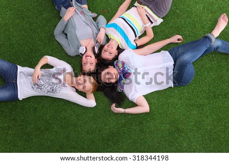 Young women lying on the grass  - stock photo