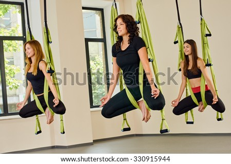 Young women making antigravity yoga exercises. green hammocks - stock photo