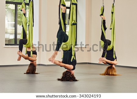 Young women making upside down antigravity yoga exercises. green hammocks