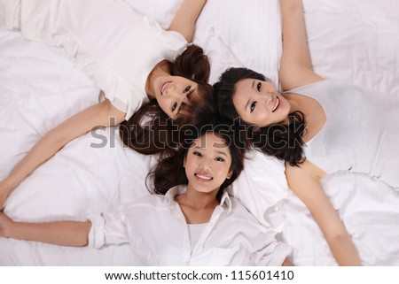 Young women on bed and isolated on pure background - stock photo