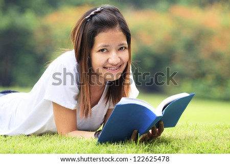 Young women open a book, look to the camera in outdoor
