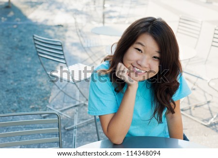 Young women outside sitting at a table smiling - stock photo
