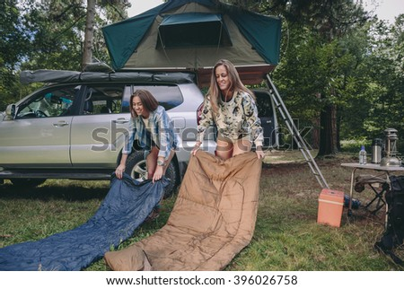 Young women placing sleeping bags over the grass in campsite with their vehicle in the background - stock photo