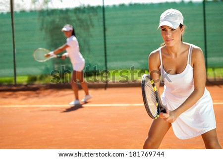 young women playing doubles at tennis at the tennis court - stock photo