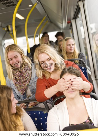 Young women playing peek-a-boo on the bus - stock photo