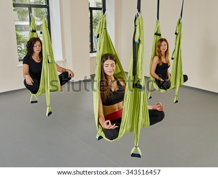 Young women posing in anti-gravity aerial yoga green hammock. indoor fitness club. break relax. shot from above