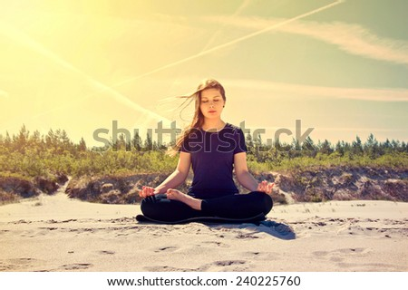 Young women practices yoga on the sand.  - stock photo
