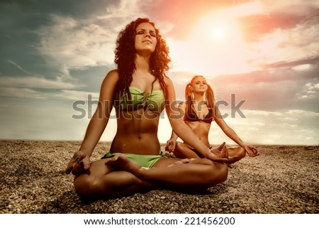 Young women practicing morning meditation in nature at the beach - stock photo