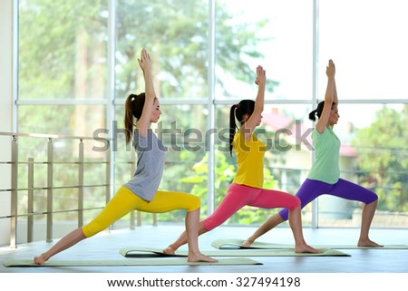 Young women practicing warrior yoga pose - stock photo