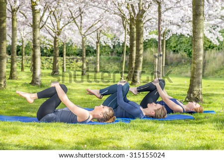 Young women practicing yoga in a blooming spring park - stock photo