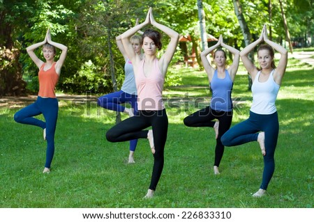 Young women practicing yoga in the park - tree pose. - stock photo