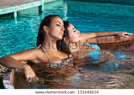 young women relaxing in outdoor jacuzzi by the pool summer day - stock photo