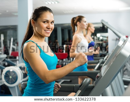 young women running on a treadmill, exercise at the fitness club - stock photo