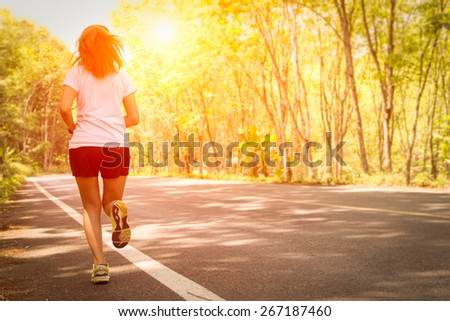 Young women running on rural road during sunset