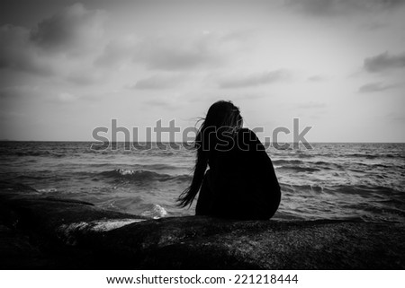 Young women siting alone on a rock at the beach,Sad concept - stock photo