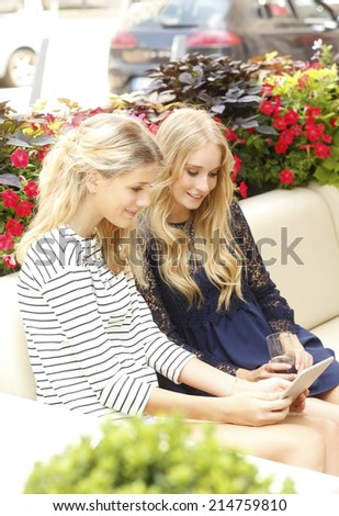 Young women sitting at coffee shop and using digital tablet. City life.  - stock photo