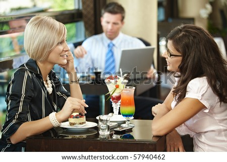 Young women sitting at table in cafe having sweets,talking. - stock photo