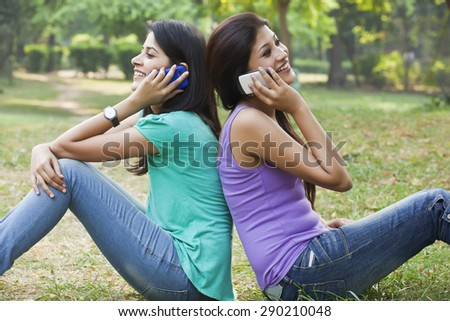 Young women sitting back to back while talking on cell phone - stock photo