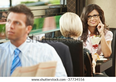 Young women sitting in cafe having sweets. Businessman reading newspaper in the forground. Selective focus on women. - stock photo