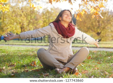 Young Women Sitting In Park With Arms Outstretched.