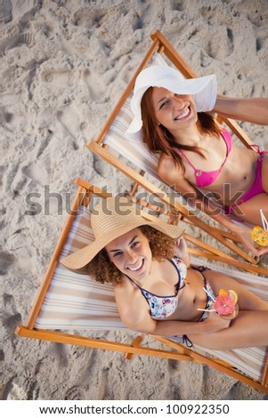 Young women sitting on deck chairs on the beach while laughing together