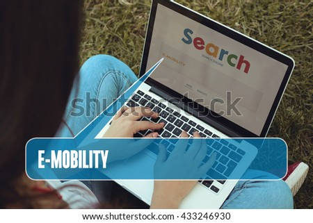 Young women sitting on the grass on a Tablet PC is searching for E-Mobility.