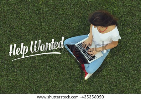Young women sitting on the grass on a Tablet PC is searching for Help Wanted. - stock photo