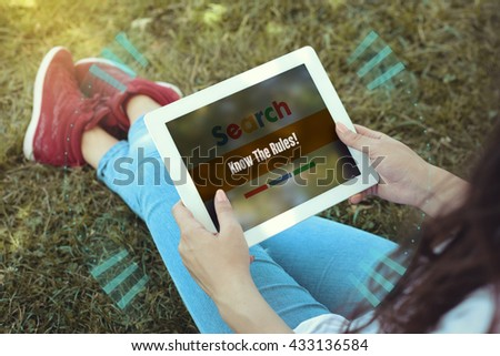 Young women sitting on the grass on a Tablet PC is searching for Know The Rules!. - stock photo