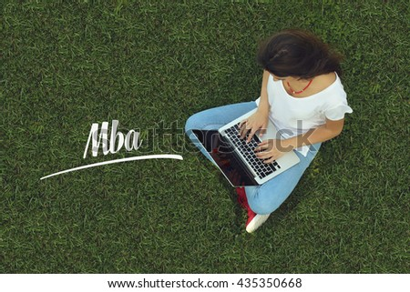 Young women sitting on the grass on a Tablet PC is searching for Mba. - stock photo