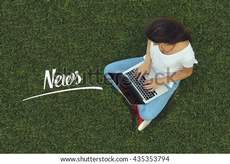 Young women sitting on the grass on a Tablet PC is searching for News. - stock photo