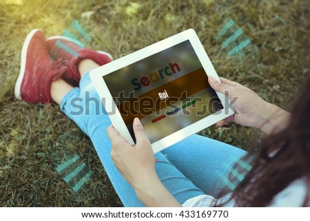 Young women sitting on the grass on a Tablet PC is searching for Roi. - stock photo