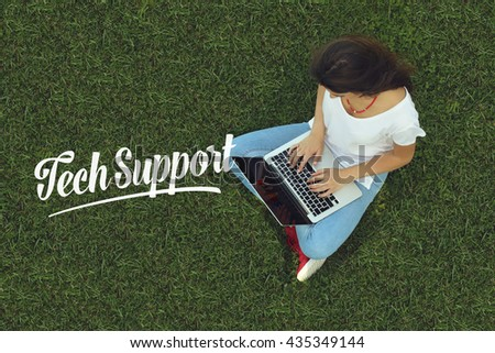 Young women sitting on the grass on a Tablet PC is searching for Tech Support. - stock photo