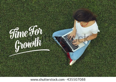 Young women sitting on the grass on a Tablet PC is searching for Time For Growth. - stock photo