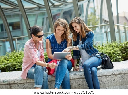 Young women sitting outdoors, using tablet smiling happy.