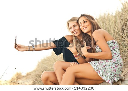 Young women smiling while they're making a photo - stock photo