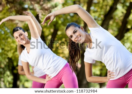 Young women stretching on aerobics class, outdoor - stock photo