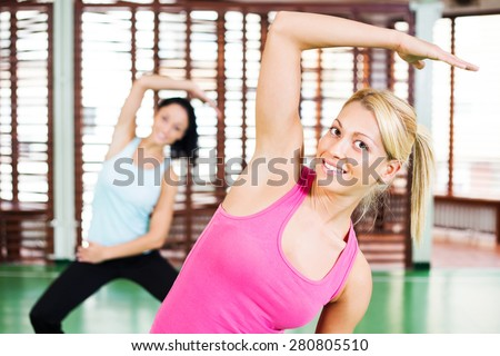Young women stretching their bodies in gym - stock photo