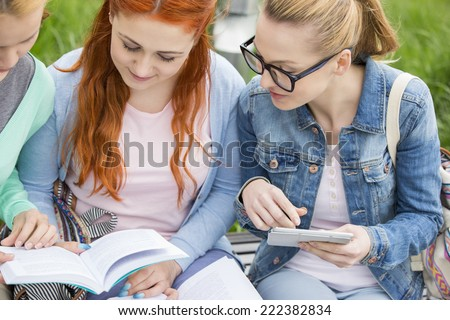 Young women studying together in park - stock photo
